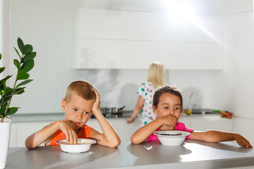 Happy young family, mother with two children, adorable toddler girl and funny messy boy having healthy breakfast eating fruit and dairy, sitting in a white sunny kitchen with window