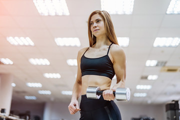 Photo of athletic young female with dumbbell isolated on light gym background. Attractive fitness woman with dumbbell sport.