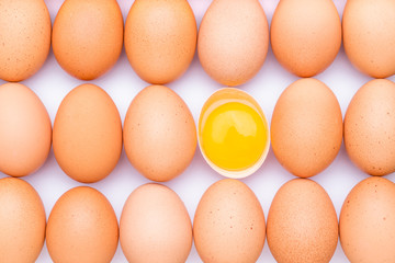 Rows of brown organic eggs and one opened egg with egg yolk on a white background.