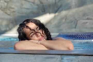 Portrait, schöne reife Frau im besten Alter mit dunklen Locken entspannt sich glücklich aufgestützt auf den Rand des Wellness Pool