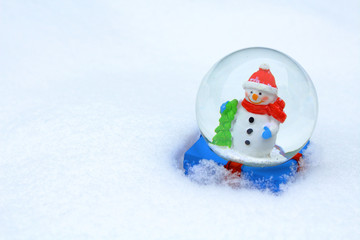 Glass ball with a snowman inside in the snow. Close-up. Background. Texture.