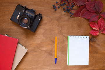 film camera on a wooden background with books and notebook