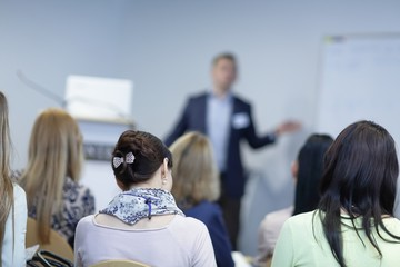 background image of a businessman speaking at a business seminar.