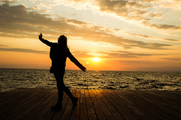 dark silhouette of dancing adult girl on wooden deck waterfront sea district in romantic orange sunset time with horizon nature landscape background, travel concept