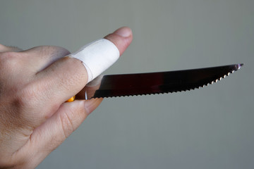 A sharp knife with notches in the hand of a man with a wounded finger. On a light background