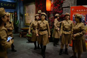 Women dressed in historical Chinese military costumes prepare to take pictures at Andong Old Street in Dandong