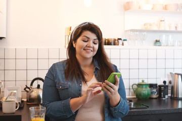 Cheerful beautiful young brunette overweight woman browsing social media on her mobile phone, chatting with friends and leaving comment under nice pic while drinking fresh orange juice in kitchen