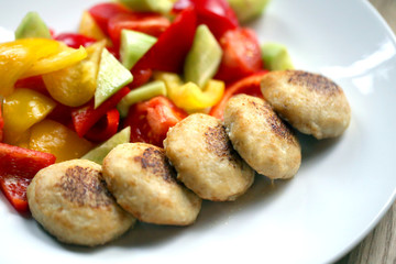 Macro photo of delicious pike burgers with vegetables on a white plate