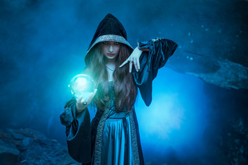The witch with magic ball in her hands causes a spirits