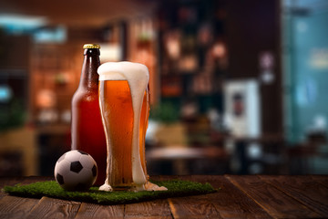 Photo of buttle and glass of beer, soccer ball on green grass