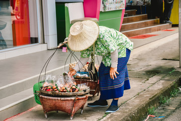 Asia people wear hats, green shirt,put on blue skirt and black shoes. She was bent down arrange food in the basket on the pavement.