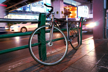 Bicycle park on footpath with street traffic background