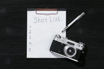 Shot list mockup. Vintage film photo camera paper page on black wooden table background.