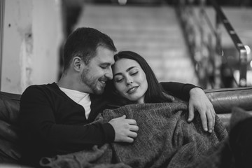 Loving girl and her boyfriend hug sitting in the sofa under the blanket in the romantic cafe. Black and white photo