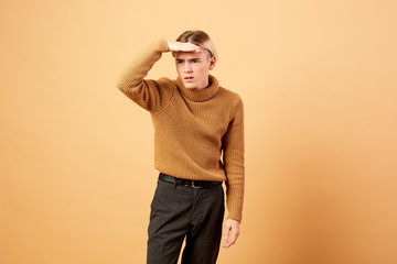 Young blond guy dressed in mustard color sweater and black pants is posing with his hand on his forehead in the studio on the beige background