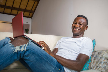 attractive and happy successful black afro American man networking with laptop computer at living room couch smiling cheerful and satisfied in internet business success