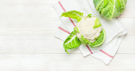 Fresh raw cauliflower, kitchen towel on rustic white wooden background top view flat lay copy space. Cooking, healthy wholesome food, vegetable, diet concept.