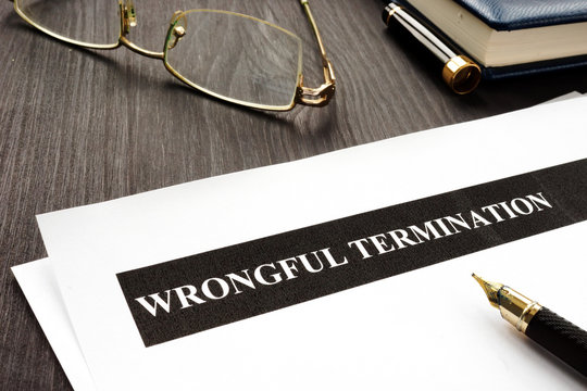 Documents about Wrongful termination on a wooden desk.