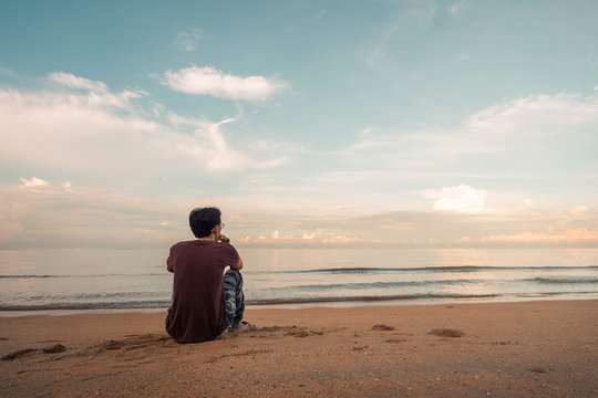 Lonely asian  man sitting watching sunset alone on beach.