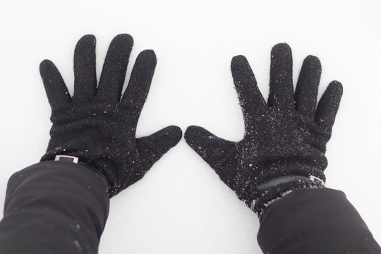 Female hands in black gloves in the snow close up