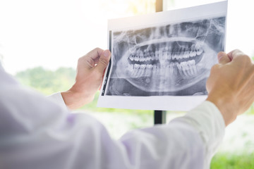 Panoramic dental X-ray of a human jaw holding in the hands of the dentist.