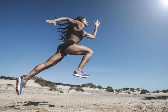 Female athlete running on desert landscape against clear sky