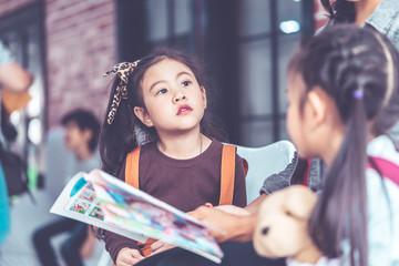 Teacher is reading story book to kindergarten students