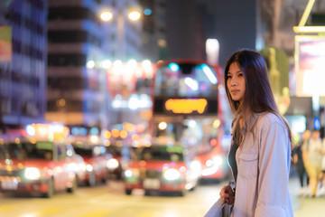 Cute Asian traveler girl in the night street of Hong Kong