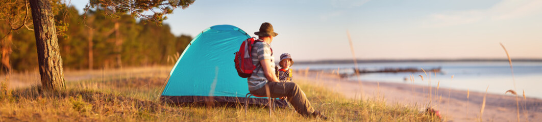 Family resting with tent in nature at sunset Wall mural