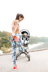 Active mother jogging. Jogging or power walking woman with pram. mom  kneads his legs whill walking with baby in stroller