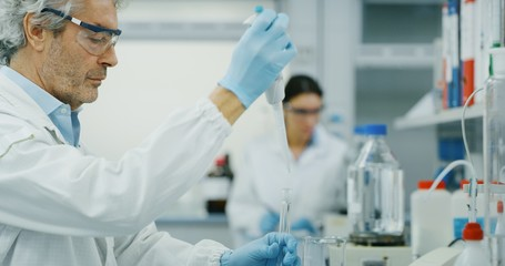 Portrait of male scientist with a pipette analyzes a liquid to extract the DNA and molecules in the test tubes in laboratory. Concept: research,biochemistry, pharmaceutical medicine