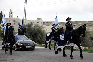 The convoy of Pierbattista Pizzaballa, the acting Latin Patriarch of Jerusalem, is escorted by mounted Israeli policemen in Jerusalem, as Mar Elias monastery is seen in the background, before his crossing into Bethlehem