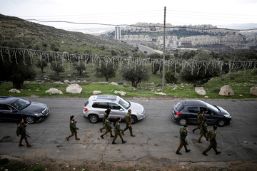 Jewish settlement of Har Homa is seen in the background as Israeli soldiers walk next to the convoy of Pierbattista Pizzaballa, the acting Latin Patriarch of Jerusalem, as it makes its way from Jerusalem into Bethlehem