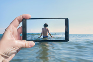 Female taking a picture of dancing boy in the headphones on the beach on the phone. Travel and family concept