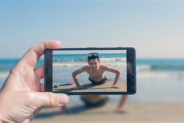 Female taking a picture of a boy on the beach on the phone. Teen boy wrung out on the sand. Travel and family concept