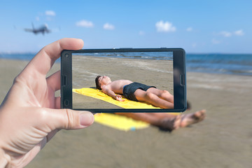 Female taking a picture of a boy in the yellow towel on the beach on the phone. Travel and family concept