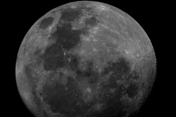 Big Moon taken with telescope in waxing gibbous phase in the dark space background.
