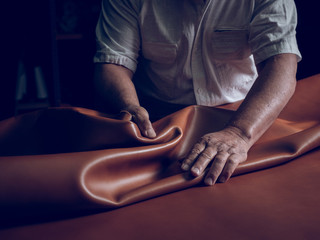 Midsection of craftsman laying leather on table