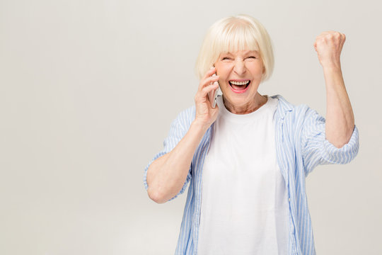Portrait of a cheerful senior woman gesturing victory isolated over white background. Using phone.