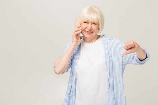 Senior caucasian woman talking on the phone isolated over white background with angry face, negative sign showing dislike with thumbs down, rejection concept
