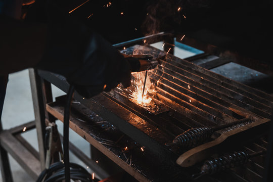 Thai Engineering student perform electric metal welding in workshop class with a lots of spark.