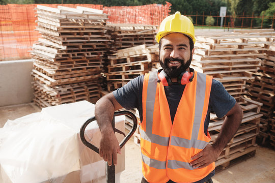 Happy Hispanic Manual Worker With Forklift Smiling At Camera
