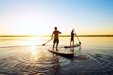 Men, friends are paddling on a SUP boards