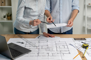 Cropped collaboration of two builder person analyzing inspect paper paperwork stand in formalwear shirt in bright loft interior workstation read civil sketch put measurement divider pencil on desk