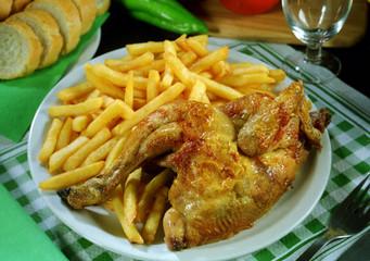 Plato combinado con medio pollo a la barbacoa con patatas fritas.