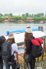 SRINAGAR, INDIA - JULY 09, 2015 : Tourist in Dal lake waiting local people use 'Shikara', a small boat for transportation in the lake of Srinagar, Jammu and Kashmir state, India