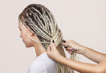A hairdresser weaves dreadlocks to a beautiful young girl in a hairdresser's.