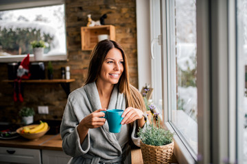 Smiling young woman in bathrobe drinking coffee in the morning, looking through window.