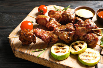 Delicious barbecued meat served with garnish and sauces on wooden board