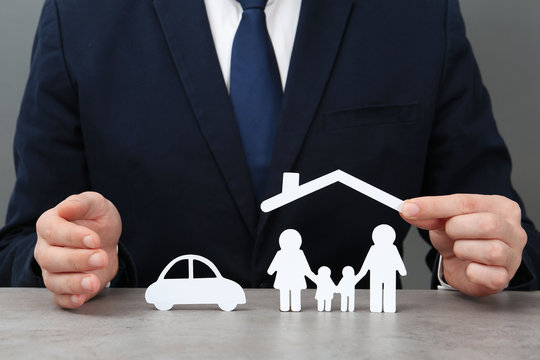 Man with cutout paper family, house roof and car at table, closeup. Life insurance concept